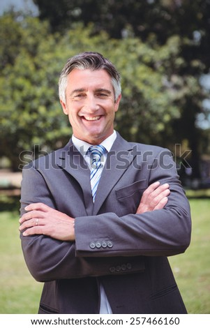 Businessman smiling in the park on a sunny day - stock photo
