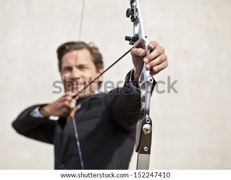 Businessman smiling while aqcuiring his target with bow and arrow - stock photo