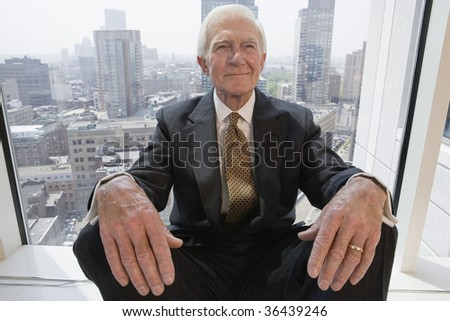 Businessman smiling while sitting in a window.