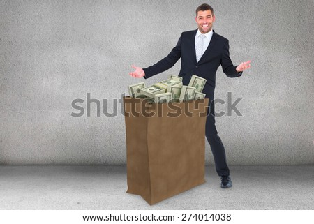 Businessman smiling with hands out against grey room - stock photo
