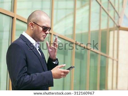 Businessman smoking and looking on cellphone