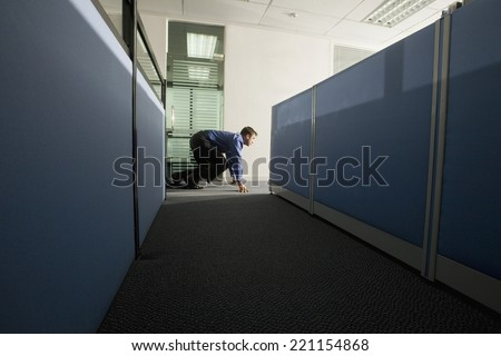 Businessman sneaking out of the office - stock photo