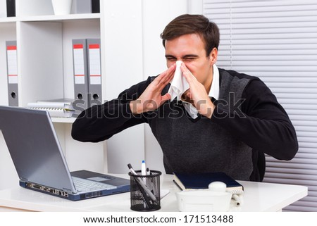 Businessman sneezing while working in his office,Businessman having flu - stock photo