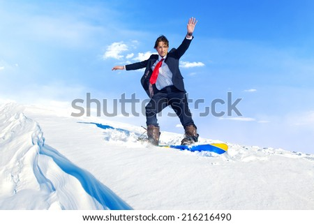 Businessman snowboarding on top of a mountain.  - stock photo