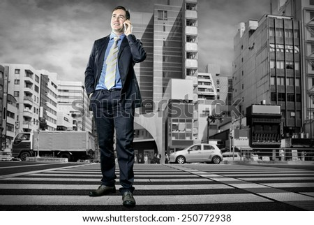 Businessman speaking by phone on the crossroad - stock photo