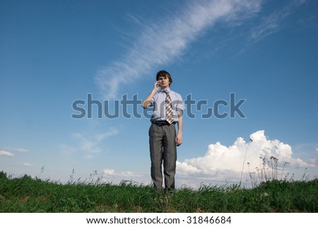 Businessman speaking on a mobile isolated over the blue sky