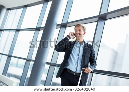 Businessman speaking on the phone at the airport - stock photo