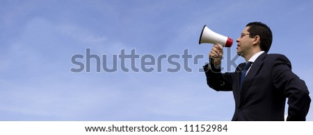 Businessman speaking with a megaphone with the blue sky as background (wide format photo) - stock photo