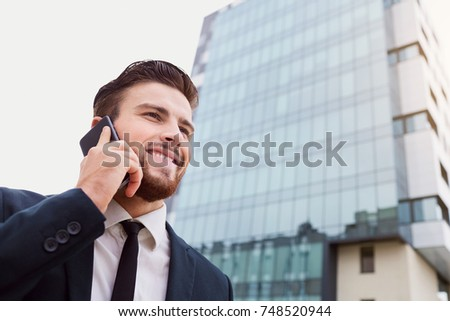 Businessman speaks on the phone outdoors