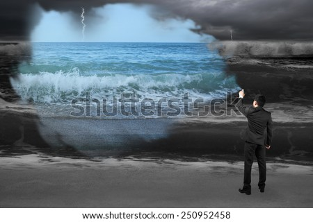 Businessman spraying calm sea paint covered dark stormy ocean background
