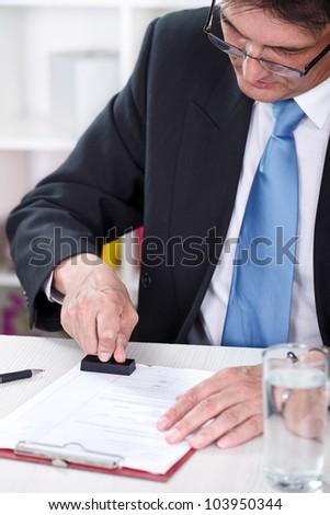 businessman stamping document in office - stock photo