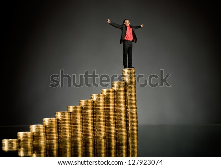 businessman stand on top of  many rouleau gold  monetary  coin, on dark background - stock photo