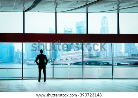 Businessman standing against room with large window looking on city - stock photo