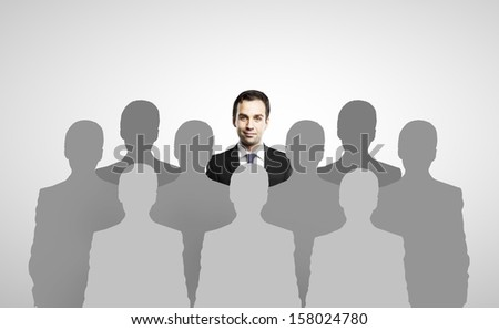 businessman standing among people silhouettes - stock photo