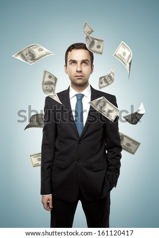 businessman standing and falling dollar on a blue background
