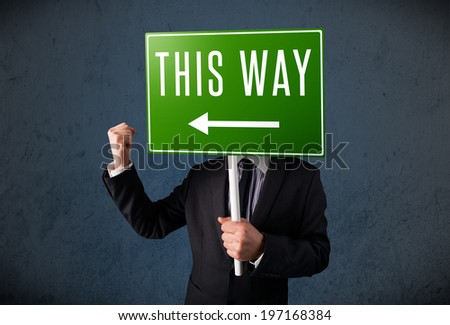 Businessman standing and holding a green direction sign in front of his head - stock photo