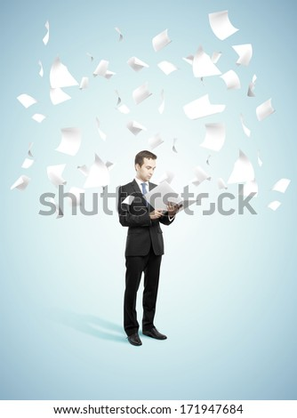 businessman standing and holding book with flying around papers
