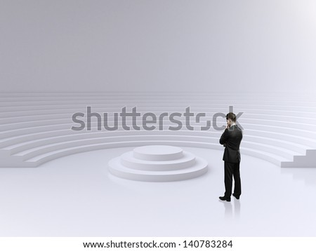 businessman standing and looking on a podium in circle auditorium - stock photo