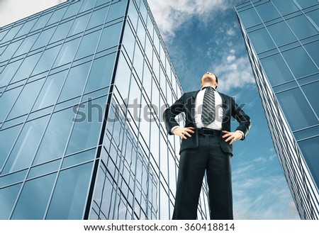 businessman standing and looking on skyscraper - stock photo