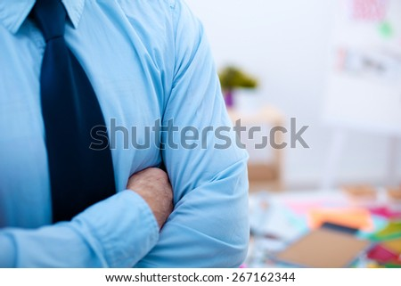Businessman standing arms crossed - stock photo