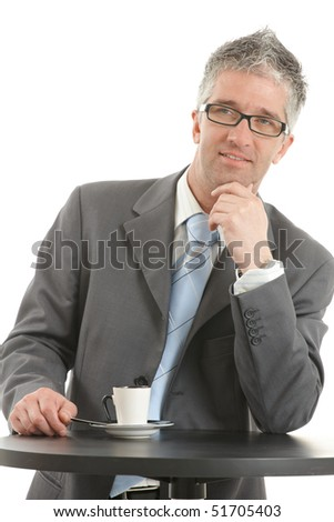 Businessman standing at coffee table, leaning on hand, thinking. Isolated on white.