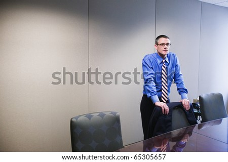 Businessman standing at conference table - stock photo
