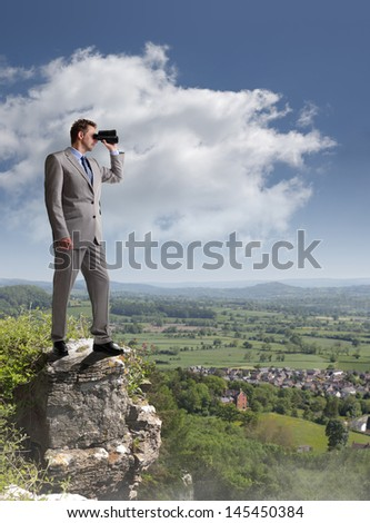 Businessman standing at the edge of a cliff looking through binoculars concept for job search, business vision or looking to the future - stock photo