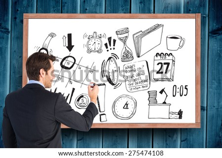 Businessman standing back to camera writing with marker against blackboard with copy space on wooden board - stock photo