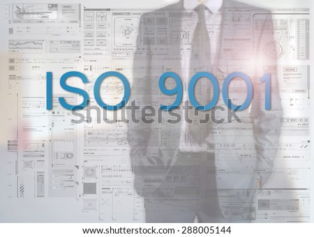 Businessman standing behind transparent board with diagrams and text ISO 9001 - stock photo