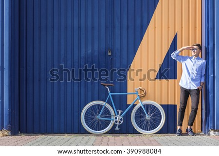 Businessman standing beside his bicycle and waiting for somebody - stock photo