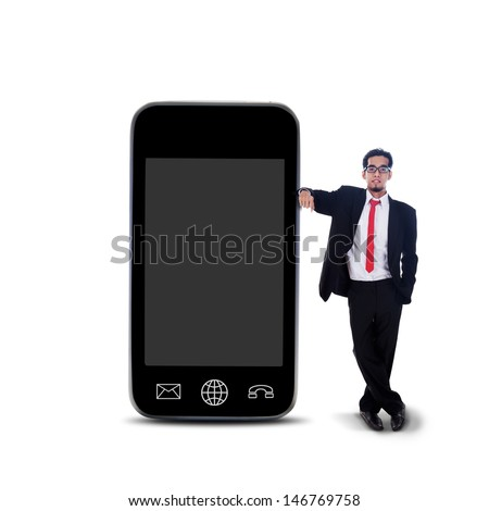 Businessman standing beside large smartphone on white background - stock photo