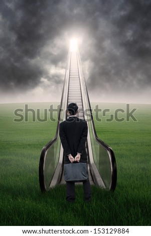 Businessman standing by an escalator in meadow - stock photo