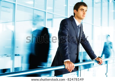Businessman standing by banisters with walking people on background - stock photo