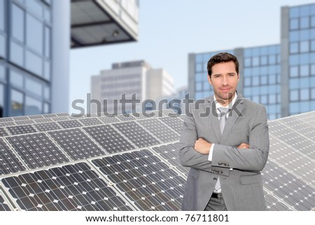 Businessman standing by photovoltaic installation - stock photo