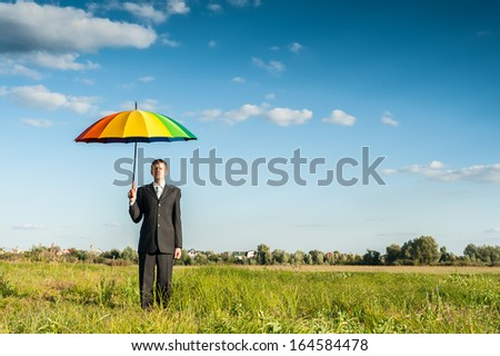 Businessman standing in a green field with multicolored umbrella. - stock photo