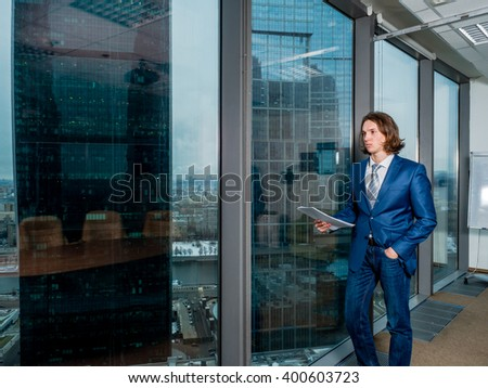 Businessman standing in an office near the panoramic windows with views of Moscow