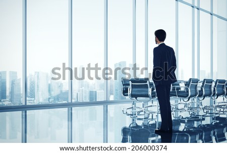 Businessman standing in bright modern office with large windows - stock photo