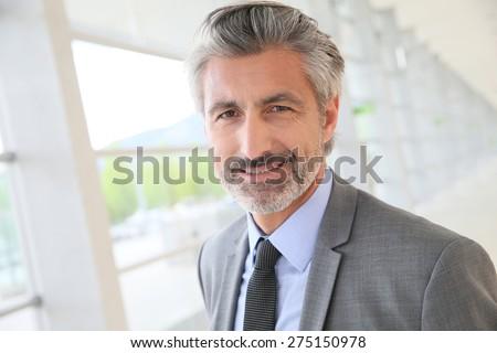 Businessman standing in building hallway - stock photo