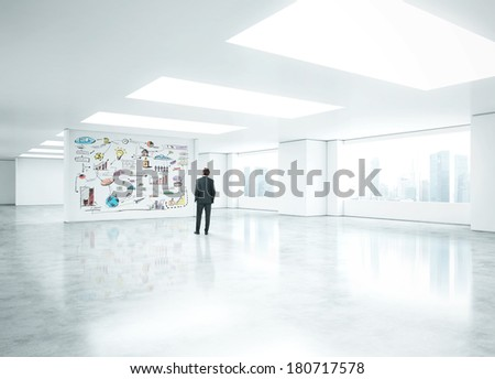 Businessman standing in empty office and looking at business strategy - stock photo