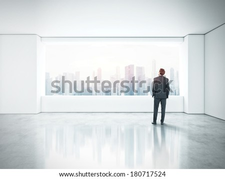 Businessman standing in empty office and looking through window - stock photo