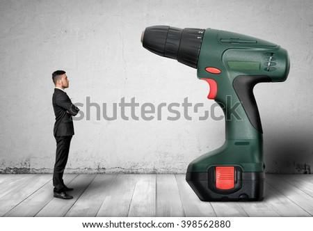 Businessman standing in front of a increased green hand drill - stock photo