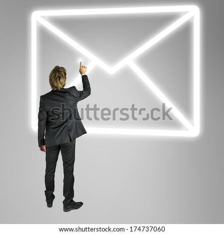 Businessman standing in front of an envelope mail icon on a virtual screen or interface conceptual of online contact and communication - stock photo