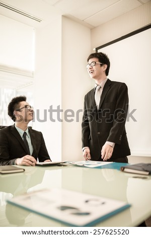 Businessman standing in front of colleagues during a meeting.Asian - stock photo