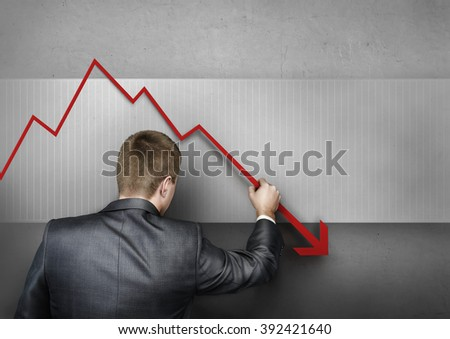 Businessman standing in front of graph and by hand draws it down.