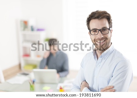 businessman standing in front of his colleagues in office - stock photo