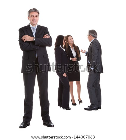 Businessman Standing In Front Of His Colleagues Over White Background