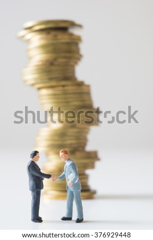 Businessman standing in front of risky coin stack. Financial crisis concept. - stock photo