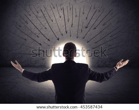 businessman standing in front of the huge gate with drawn arrows pointing to the entrance - stock photo