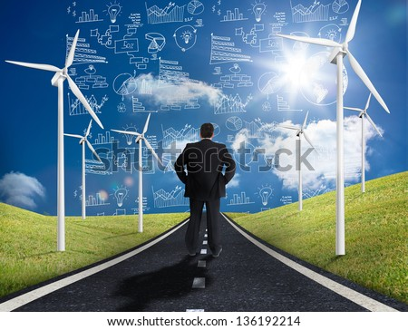 Businessman standing in middle of road with wind turbines either side looking at graphs on the horizon - stock photo