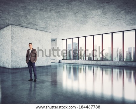 Businessman standing in modern bright office - stock photo
